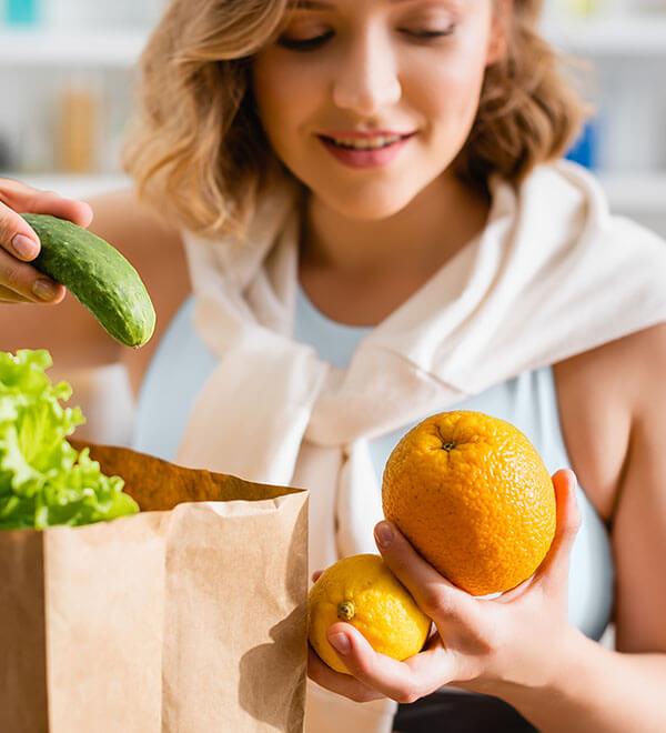 Mujer con dos naranjas, fuente de vitamina C