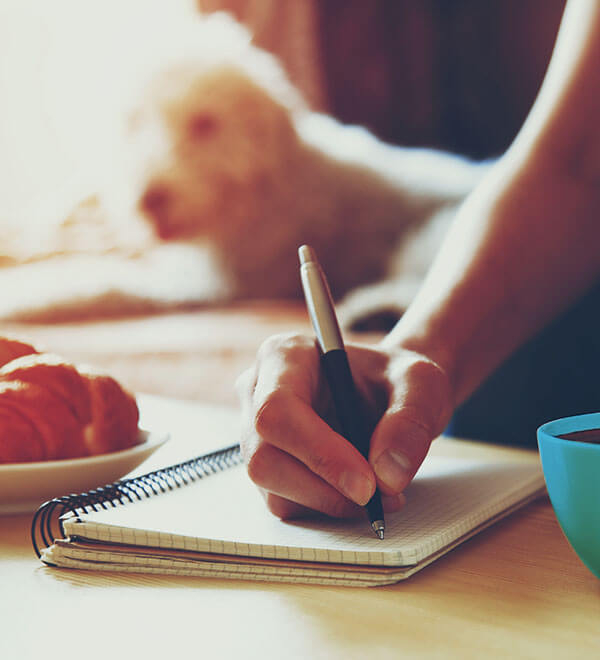 Woman working from home with to do list and pen