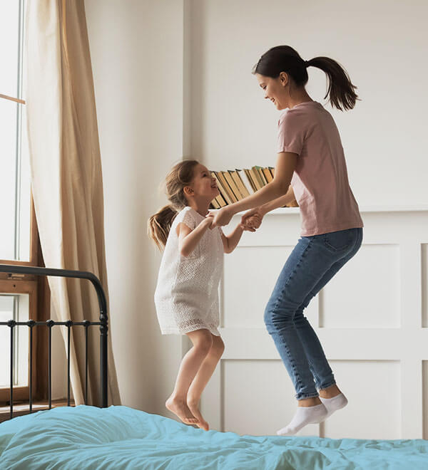Young woman and girl jumping on bed