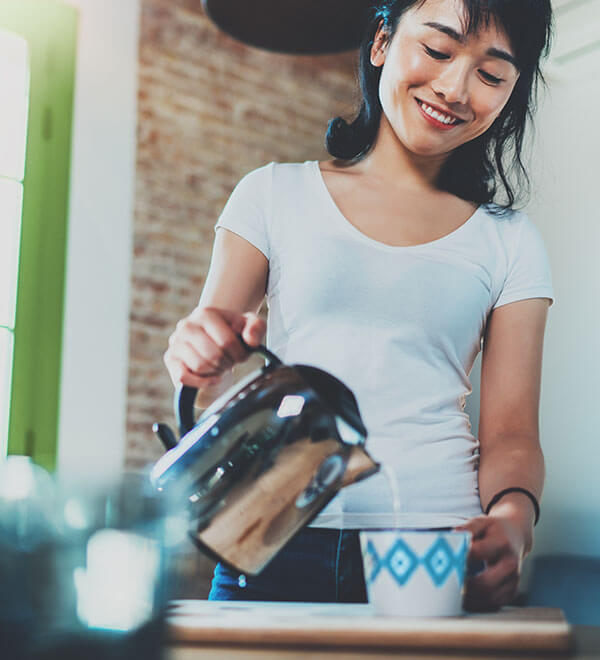Young woman making cup of tea in kitchen