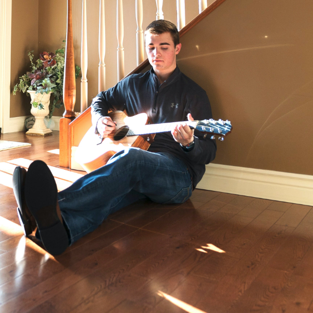 Person sitting on floor playing the guitar