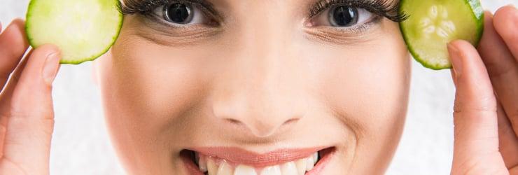 Vrouwengezicht met twee schijfjes komkommer bij haar ogen