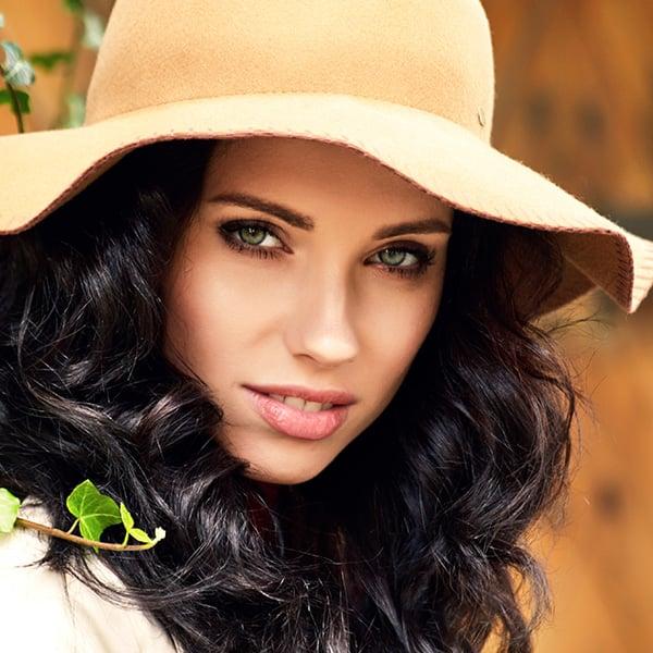 volto di ragazza bruna con cappello e occhi verdi