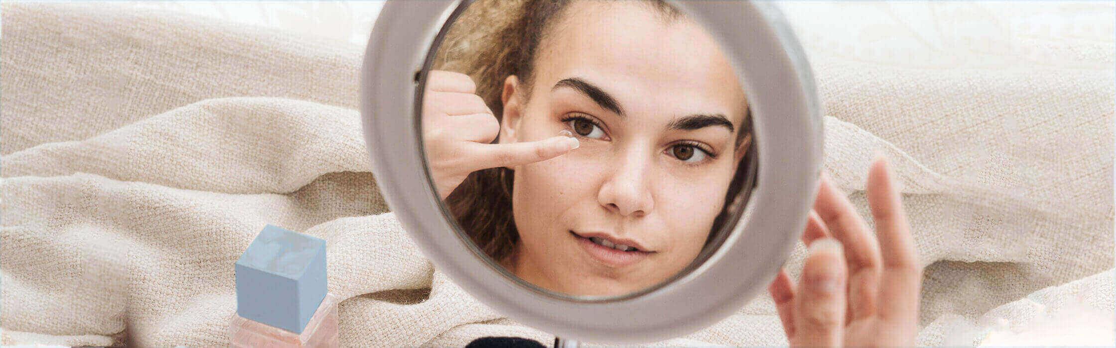 Closeup of woman holding contact lens