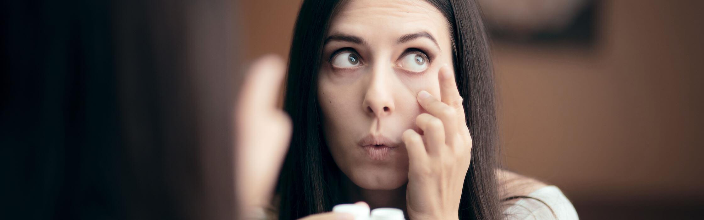 Een vrouw probeert een lens uit haar oog te halen