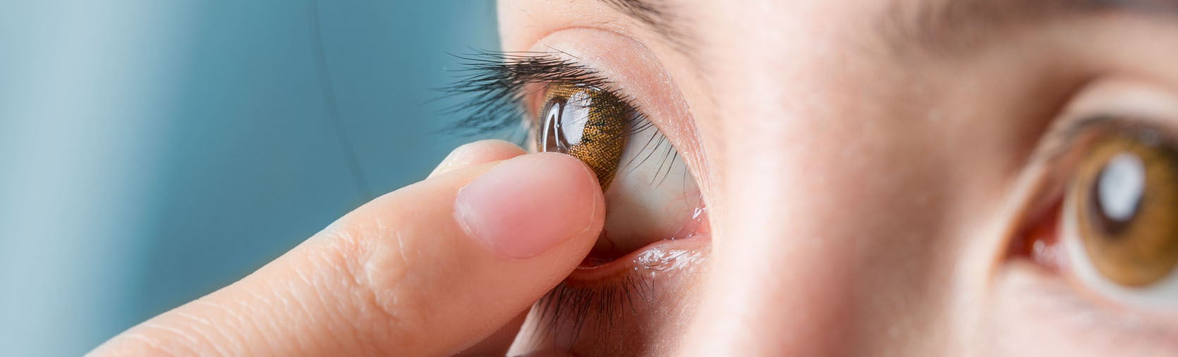 Woman removing a stuck contact lens