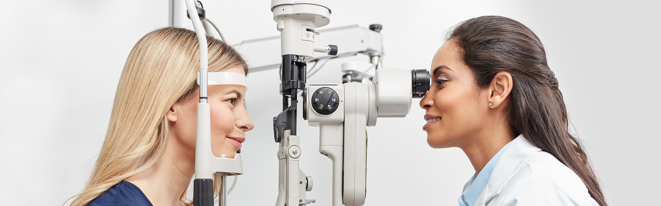 Optician and customer looking through a tonometer