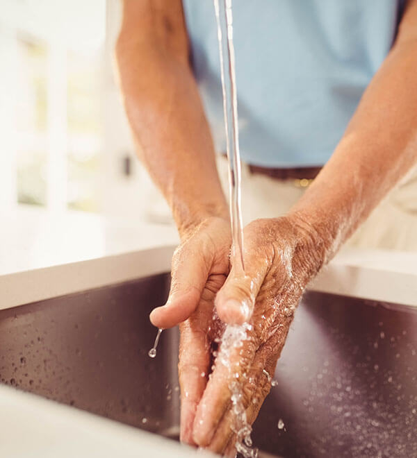 A man washing his hands in a sink