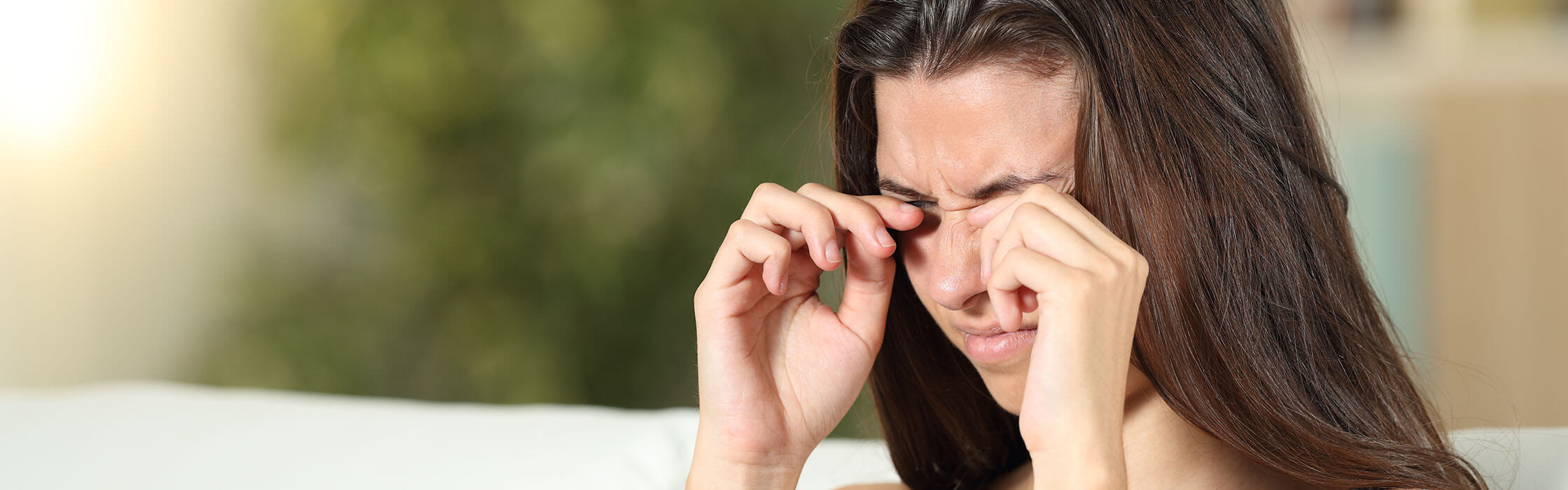 A woman itching their eye, infected with conjunctivitis