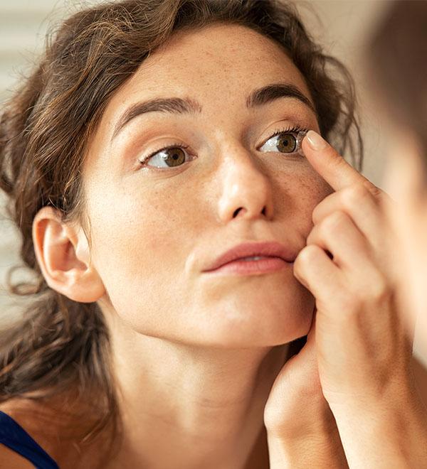 Woman applying contact lenses