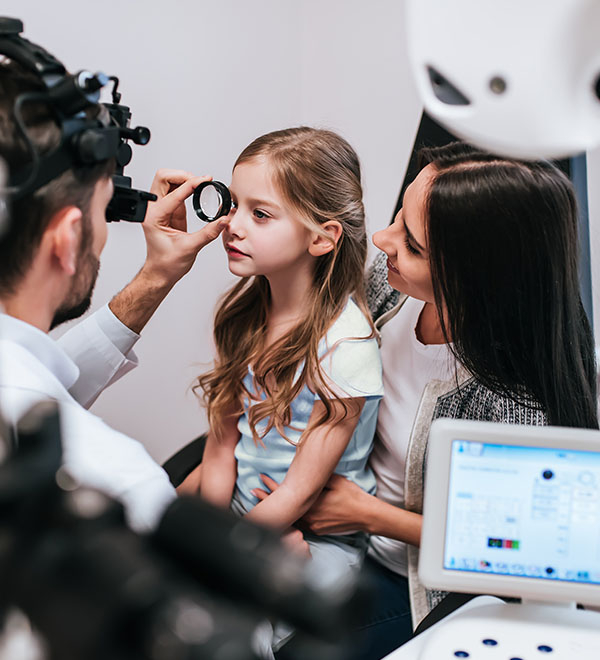 Optician performs eye test on a child