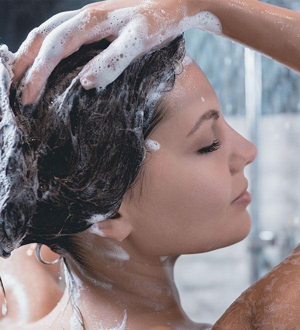 Een vrouw wast haar haar onder de douche