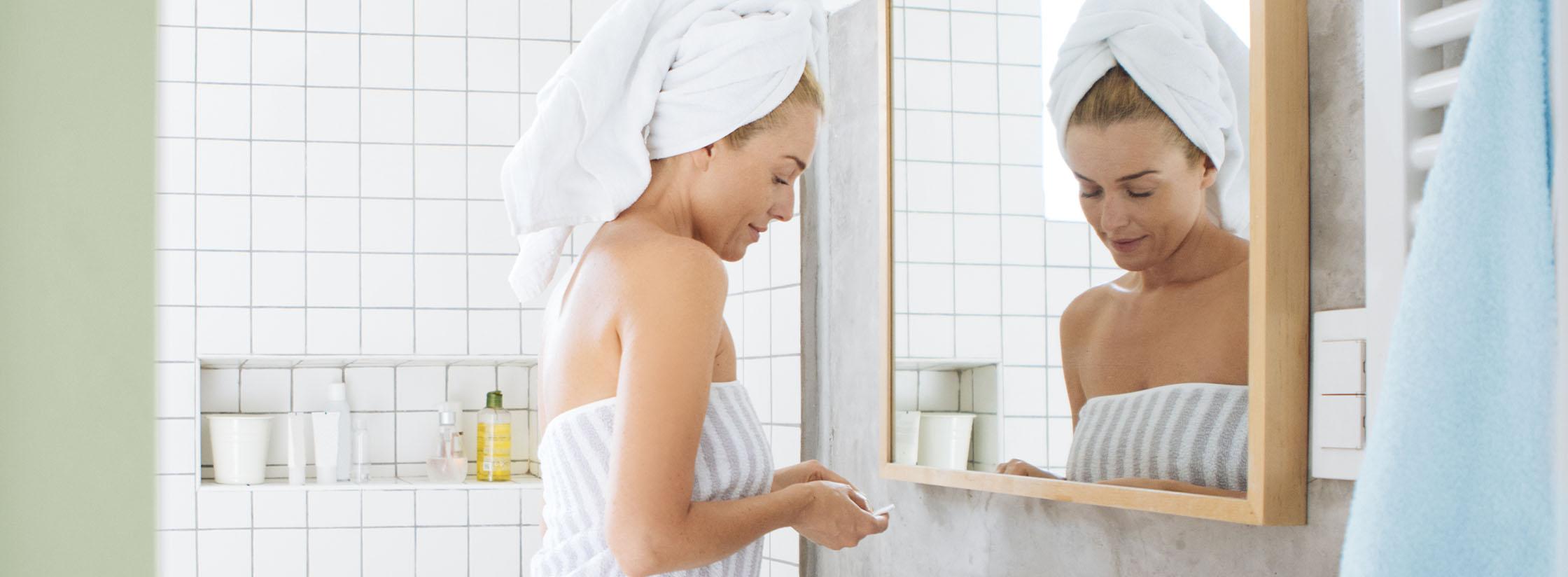 Een vrouw staat voor de spiegel in de badkamer