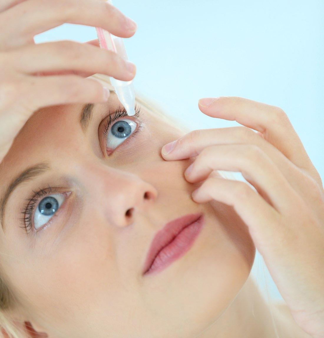 Mujer echándose lágrimas artificiales